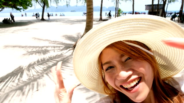 4k shot : asian woman with smile face is walking on the beach and coming to say hi to everyone. the perfect location that has shadow of coconut tree on sand in sunny day. - swimwear stock videos & royalty-free footage