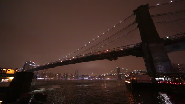 vídeos de stock, filmes e b-roll de shot at night overlooking the east river and the brooklyn bridge as a boat crusies by. - rio east
