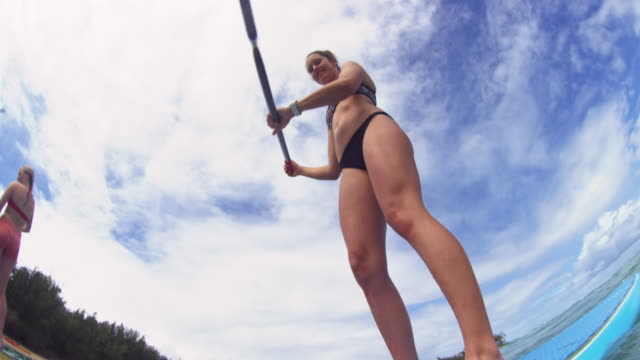 Shot at water level of girl on a SUP paddling by camera