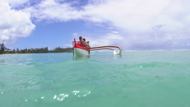 shot at waterlevel of four people paddling in outrigger - turtle bay hawaii stock videos and b-roll footage