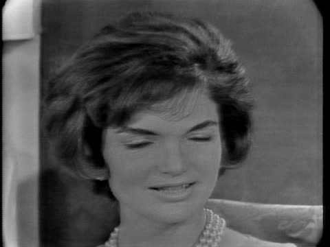 shot begins with close up of jacqueline kennedy, who has short hair and is wearing a dress and a pearl necklace. she has a microphone hanging around... - jackie kennedy stock videos & royalty-free footage