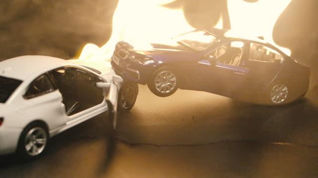 slo mo shot auto modell unfall simulation brennen flamme feuer schwarz hintergrund - unfall ereignis mit verkehrsmittel stock-videos und b-roll-filmmaterial