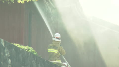 october 31, 2019 location: naha city, okinawa prefecture, japan shot list: a firefighter draining water off toward shuri castle destroyed by fire... - unesco world heritage site点の映像素材/bロール