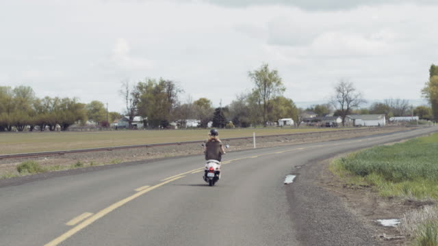 shot following woman riding down country road on a scooter - moped stock videos and b-roll footage