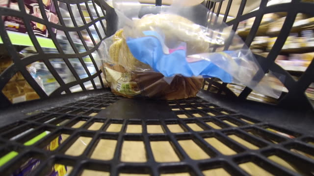 POV shot from a basket as a shopper places food items into it.