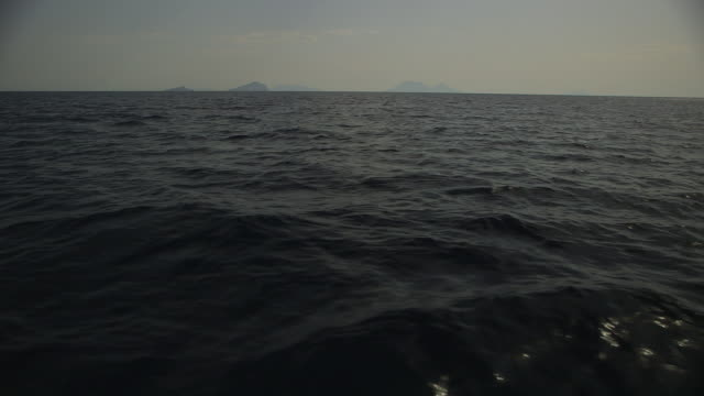 POV shot from a boat sailing on dark water near Aeolian islands, Italy.
