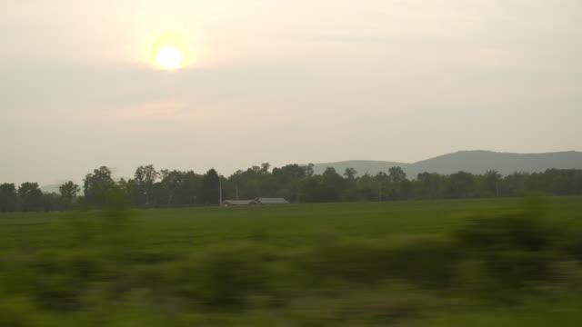 POV shot from a car window of fields in Pennsylvania, USA.