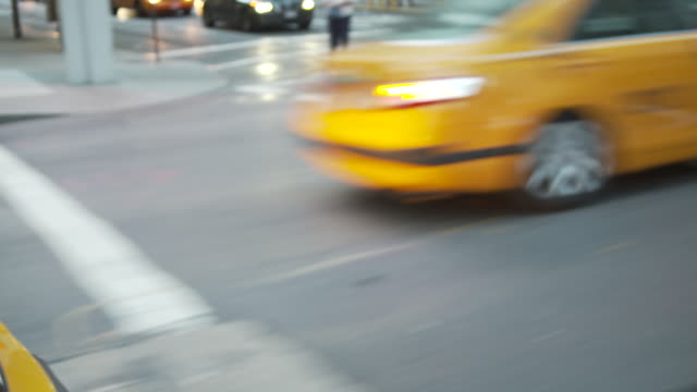 POV shot from a car window of out-of-focus yellow taxis driving past, New York City, USA.