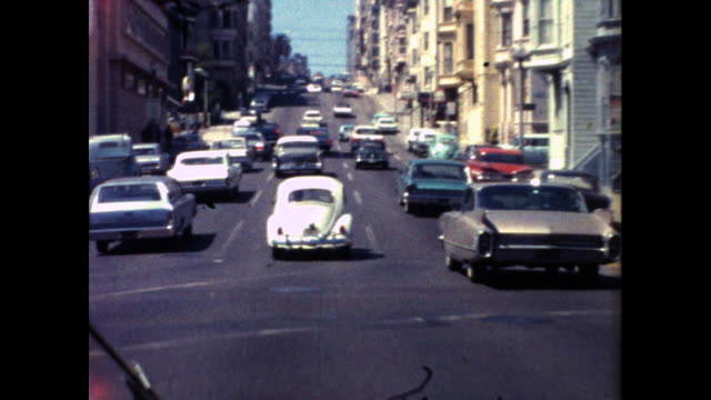 shot from a moving car driving on a busy street in san francisco; cars parked beside the sidewalk, tall buildings and hills - the cars stock videos & royalty-free footage