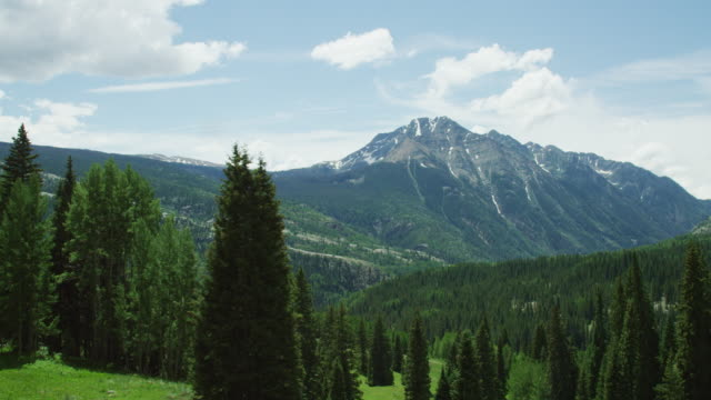 shot from a moving vehicle of the san juan mountains in colorado as seen from red mountain pass (million dollar highway/us 550) through the rocky mountains in summer on a partly cloudy day - colorado stock videos & royalty-free footage