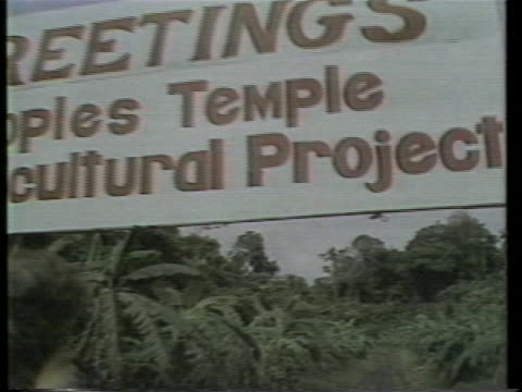 "shot from a vehicle driving through the entrance to jonestown zoom in on sign that says ""greetings peoples temple agricultural project"" this is from... - 1978 stock videos & royalty-free footage"