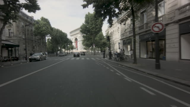 POV shot from a vehicle driving up Avenue Victor-Hugo toward the Arc de Triomphe in traffic in Paris, France