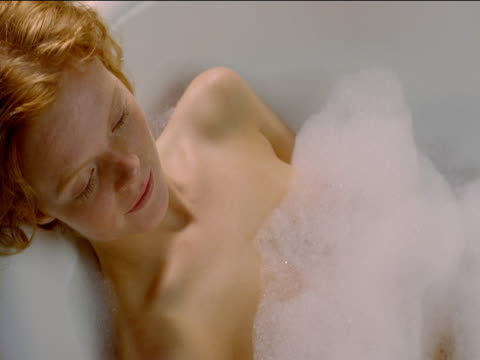 shot from above, the head and shoulders of a redhead woman relaxing in a foam-filled bath. - körperpflege stock-videos und b-roll-filmmaterial
