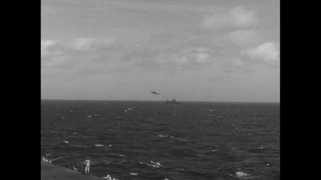 pov shot from aircraft carrier of another carrier in distance and warplane flying low over water approaching carrier and landing on carrier / note... - south pacific ocean stock videos & royalty-free footage