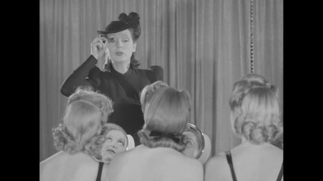 vidéos et rushes de shot from behind row of women in bathing suits sitting at makeup tables putting mascara on their eyelashes, instructor anne delafield and hairdresser... - mascara
