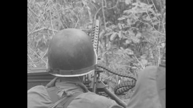 shot from behind two soldiers as they sit in position on slope looking out at mountain two soldiers walk past them / two soldiers sitting on slope... - machine gun stock videos & royalty-free footage