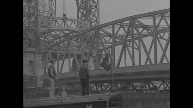 vídeos de stock, filmes e b-roll de shot from below bridge of span being added to the triborough bridge / shot from moving boat of span being placed in position tugboat in foreground /... - moving activity