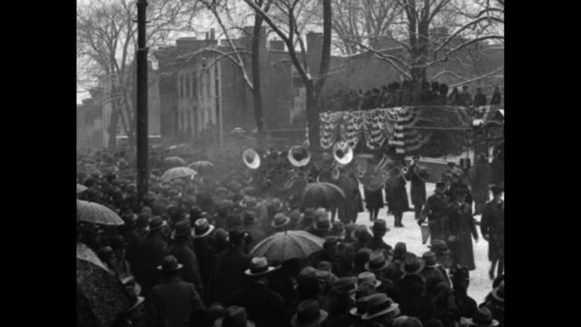 shot from below of gov. franklin d. roosevelt standing on reviewing stand watching parade, outgoing governor al smith standing to his right; snow... - 長点の映像素材/bロール