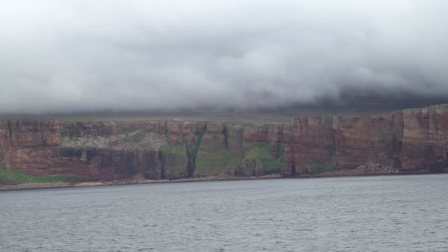 shot from ferry on the move the old man of hoy is a 449foot sea stack on hoy part of the orkney archipelago off the north coast of scotland formed... - hoy stock videos & royalty-free footage