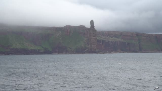 shot from ferry on the move the old man of hoy is a 449foot sea stack on hoy part of the orkney archipelago off the north coast of scotland formed... - atlantic islands stock videos & royalty-free footage