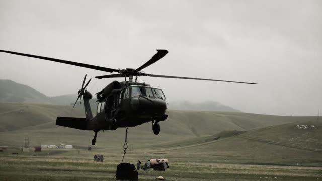 shot from field of black hawk helicopter hauling off cargo. - black hawk helicopter stock videos and b-roll footage
