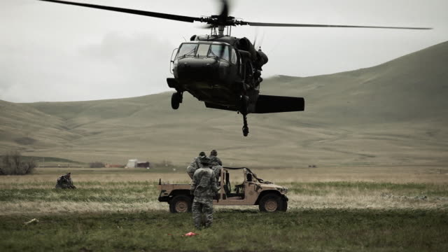 Shot from ground of Black Hawk helicopter hovering above Humvee while soldier gives signals to pilot.