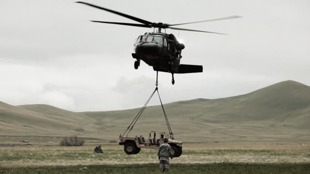 Shot from ground of Black Hawk helicopter lifting Humvee while soldier gives signals to pilot.
