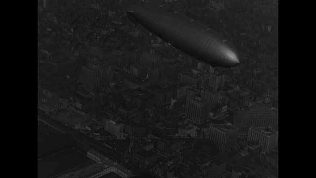 shot from ground of hindenburg in flight with swastikas on its tail clearly visible / four shots from another air vehicle of hindenburg in flight... - ヒンデンブルク号点の映像素材/bロール