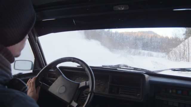 vidéos et rushes de shot from inside of car racing on snow in rural area - un seul homme