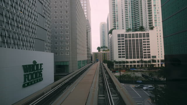 pov shot from metromover ride on elevated tracks between highrise buidlings in downtown miami - spoonfilm stock-videos und b-roll-filmmaterial