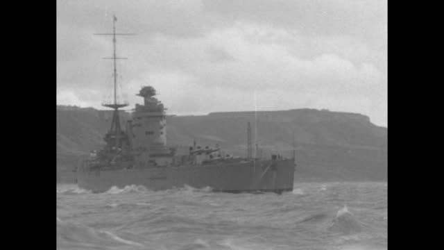 shot from moving boat of hms nelson steaming ahead, coastline in background / note: exact month/day not known - british military stock-videos und b-roll-filmmaterial