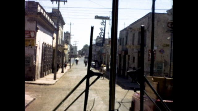 shot from moving bus of town street, people walking on the sidewalk, cars parked by the sidewalk, and telephone poles - the cars stock videos & royalty-free footage