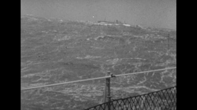 shot from moving ship of flying enterprise being towed in distance in high seas / note exact day not known - sink stock videos & royalty-free footage
