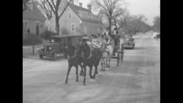shot from moving vehicle in front of coach pulled by horses rolling down street; two african-americans in 18th century livery drive, ride on the... - 18th century stock videos & royalty-free footage