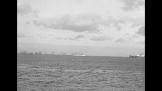 shot from on board transport of two german planes attacking / soldier on board transport firing antiaircraft gun / wide shot from transport of ships... - deutsches militär stock-videos und b-roll-filmmaterial