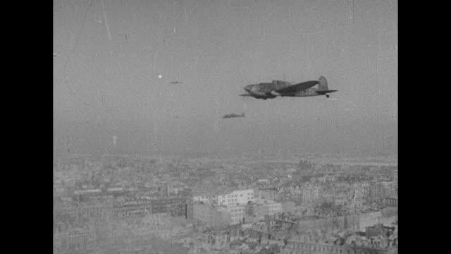 Shot from plane of Soviet warplanes flying over Warsaw / Soviet and Polish soldier raising Polish flag / Soviet and Polish soldier embracing / CU...
