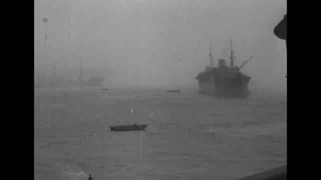 Shot from ship of explosion in harbor / wide shot from ship of landing barges heading towards shore / shot from ship of troop transport and landing...