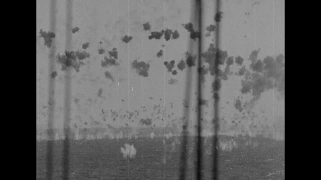 shot from ship of japanese plane diving through flak catching fire and crashing into ocean two ships in foreground / shot from ship of japanese plane... - flugabwehr stock-videos und b-roll-filmmaterial