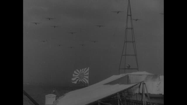 Shot from ship of Japanese warships at sea / line of Japanese warships at sea / two shots of formation of Japanese warplanes flying over ship / crowd...