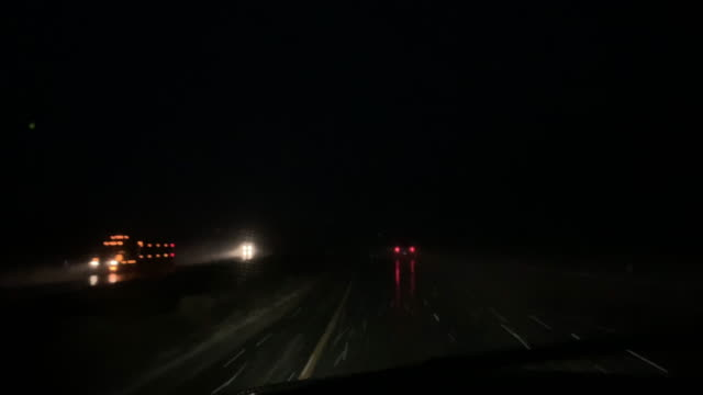 shot from the front of a moving vehicle with traffic during a snowstorm at night - autostrada interstatale americana video stock e b–roll