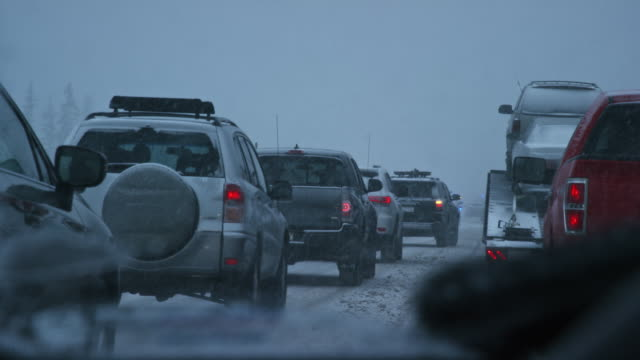 vidéos et rushes de tiré de l'avant d'un véhicule alors qu'il était arrêté par un accident et des travailleurs d'urgence sur une autoroute au cours d'une tempête de neige au crépuscule - phare arrière de véhicule