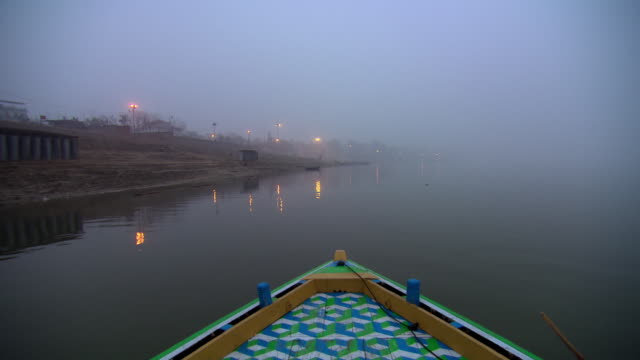 POV shot from the prow of a boat as it heads towards the city of Varanasi.