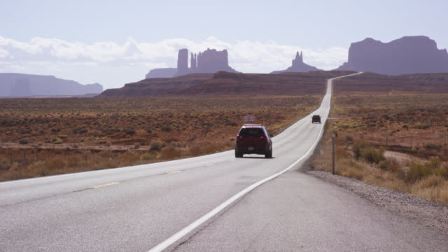 stockvideo's en b-roll-footage met shot from the side of a highway/interstate as vehicles pass by in the desert of utah and arizona on a bright, sunny day with mountains and rock formations in the distance - sports utility vehicle