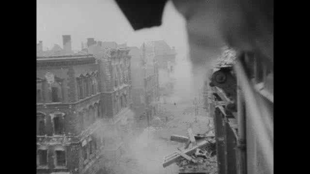 Shot from upper story of building of street filled with smoke two Soviet soldiers run across street / shot through window of building of Soviet...