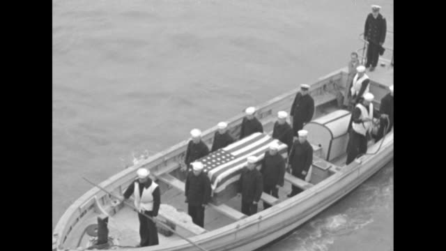 Shot from USS Augusta of motor launch carrying coffin draped in US flag and sailors as it approaches coffin contains remains of a soldier killed when...