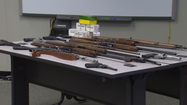 stockvideo's en b-roll-footage met shot guns hand guns and winchester bullets on a table that were seized during the arrest of alleged gun trafficker 19yearold jorge figueroa and... - pistool handwapen
