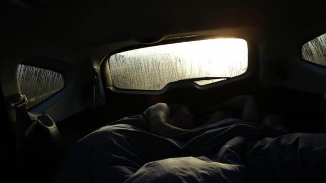 shot inside car, couple camping in car on beach, push hatch open and sunlight floods in/tarifa/andalucia/spain - heckklappe teil eines fahrzeugs stock-videos und b-roll-filmmaterial
