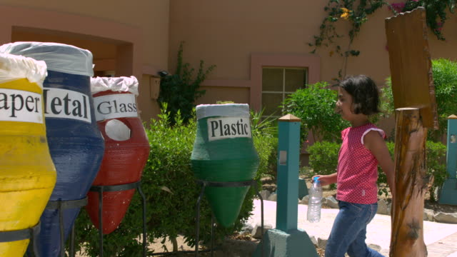 MS SLO MO PAN Shot Little Girl placing plastic bottle into recycle bin / ElGouna, RED Sea, Egypt