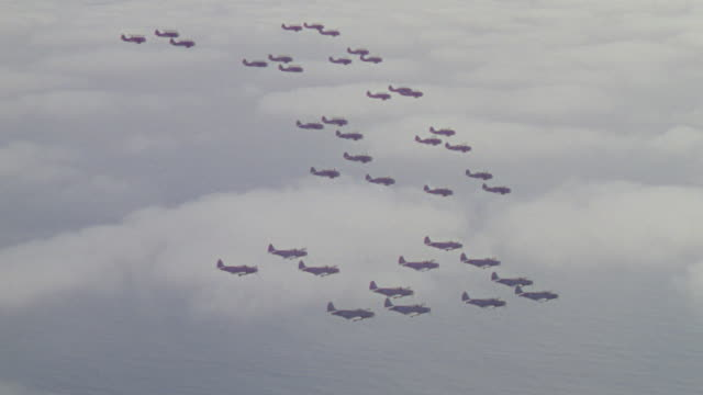 ms aerial shot looking down over planes in formation flying through clouds - formationsfliegen stock-videos und b-roll-filmmaterial