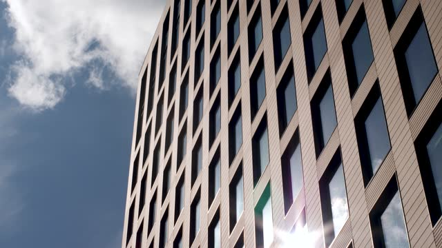 4k shot looking up at skyscraper corporate office block headquarters as dramatic grey clouds pass by giving moody dark appearance with sun reflection in glass, london, uk, europe - 1 minute or greater stock videos & royalty-free footage
